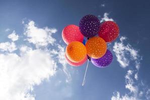 bunte Luftballons fliegen auf dem blauen Himmel foto