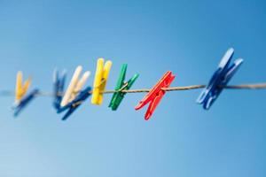 bunte Wäscheklammern auf Wäscheleine gegen blauen Himmel.