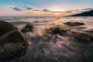 wundervoller Himmel des Sonnenuntergangs und Welle über Felsbrocken