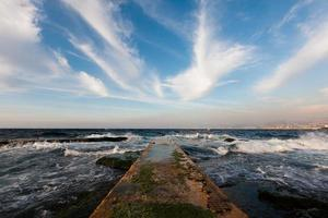 Pier und blauer Himmel mit langen weißen Wolken foto