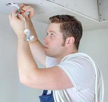 zertifizierter Elektriker installiert Steckdose für Glühbirne foto