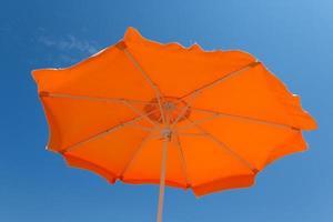 orange Sonnenschirm gegen einen blauen Himmel