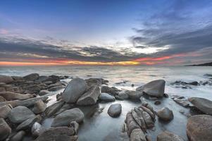 Sonnenuntergang über dem Meer. Stein im Vordergrund