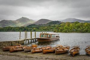 Keswick Bootslandung mit launischem bewölktem Himmel und Bergen.