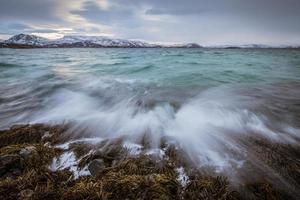Wellen krachen auf den Felsen in Sommaroy, Norwegen