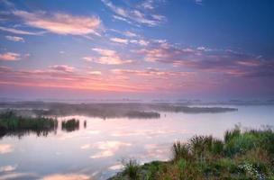 warmer Sommersonnenaufgang über dem Fluss foto