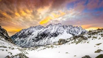 Panoramablick auf weiße Winterberge nach buntem Sonnenuntergang
