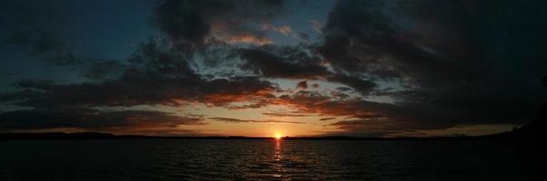 Panoramablick auf den Sonnenuntergang über dem See