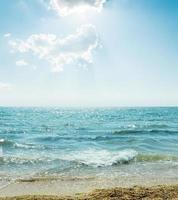 Welle auf Meer und blauem Himmel mit Wolken und Sonne foto