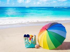 Sommerhintergrund mit Regenbogenschirm und Strandtasche