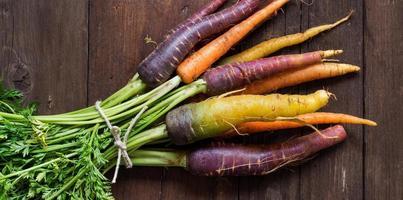 frische Bio-Regenbogen-Karotten mit Grün foto