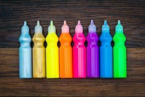 bunte Farbe - Flaschen mit bunten Pigmenten auf hölzernem Hintergrund