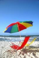 Regenbogenfarbener Regenschirm und Stühle an einem weißen Sandstrand