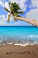 brauner Strandsand mit geschriebenem Wort willkommen foto
