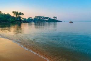 Morgensonnenstrahlen an einem schönen Strand foto