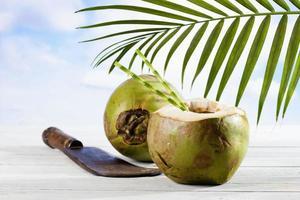Kokosnuss mit Trinkhalmen, altes Hackmesser foto