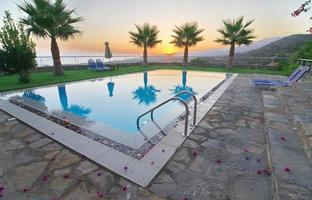 Palmen und Pool in einem ägäischen Sonnenaufgang