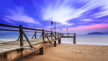 Langzeitbelichtung von buntem Sonnenaufgang und hölzernem Pier foto