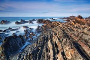 Marine Rocky Shore Ocean wäscht sich gegen einen dramatischen blauen Himmel.