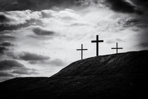 Schwarzweiss-Bild von drei Kreuzen, die auf Hügel sitzen foto