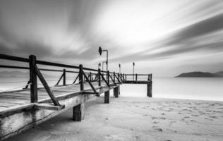 Langzeitbelichtung von magischem Sonnenaufgang und hölzernem Pier