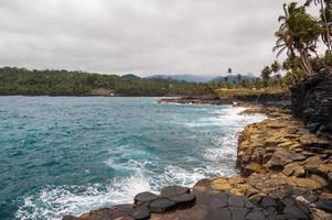 Klippen am tropischen Ufer mit Palmen und unberührtem Meer