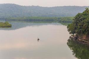 Fischer auf einem Paddelboot, das den Fluss rudert