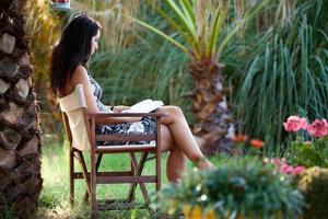 frau liest sich ein buch im tropischen garten foto