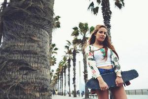 Porträt des jungen Hipster-Mädchens, das Skateboard hält