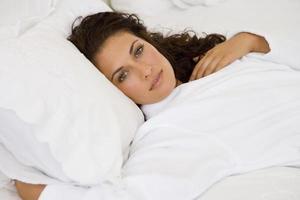 junge Frau im weißen Bademantel, im Bett liegend, Porträt