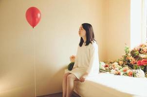 rote Luftballons und weißes einteiliges Kleid.