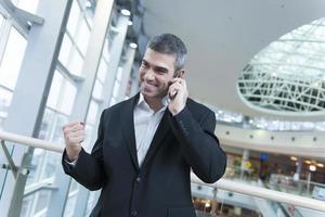 Geschäftsmann feiert das Sprechen auf dem Handy