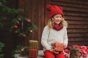 glückliches Kindermädchen, das Weihnachten draußen im gemütlichen Landhaus feiert foto