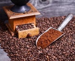 antike Mühle mit gemahlenem Kaffee in Schaufel auf Bohnen