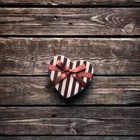 herzförmige Geschenkbox zum Valentinstag auf Holztisch. foto