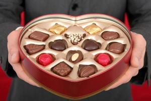 Mann hält herzförmige Schachtel mit Süßigkeiten