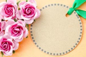 leeres braunes Papieretikett und rosa Rose für Ihren Text. foto