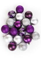 violette und silberne Weihnachtskugeln auf einem weißen Tisch