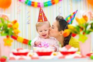 Mutter küsst sie glücklich, während Baby Geschenk überprüft