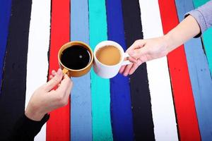 Kaffeetrinken mit buntem Paneelhintergrund.