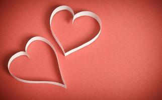 zwei Herzen des weißen Papiers, das auf einem roten Hintergrund liegt foto