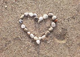 Herz von Meeresschindeln im Sand. foto
