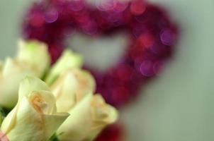 gelbe Rosen vor rotem und rosa Herz