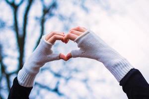 Fäustlinge Herz auf Winterhintergrund. Herzform am Valentinstag