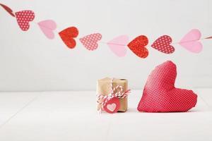 Girlande der Herzen über kleiner Geschenkbox und rotem Herzkissen foto