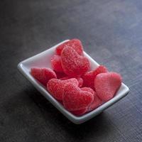 Süßigkeiten in Form von Herzen auf hölzernem Hintergrund. foto