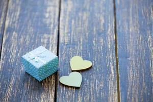 zwei Herzen formen Spielzeug und Geschenk auf hölzernem Hintergrund.