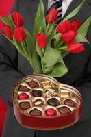 Mann hält herzförmige Schachtel mit Süßigkeiten und roten Tulpen foto