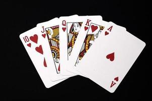 Herzen Royal Flush Hand isoliert auf schwarz foto