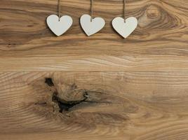 drei weiße Liebe Valentinstag Herz hängen auf Holz Textur foto